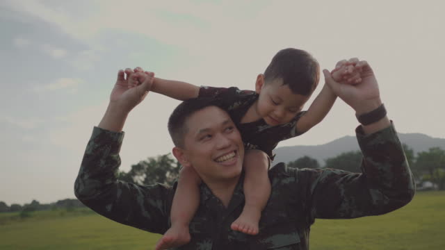 Soldier father holding and playing his son in a park Smiling army soldier and son playing in the park. Thailand. veteran stock videos & royalty-free footage