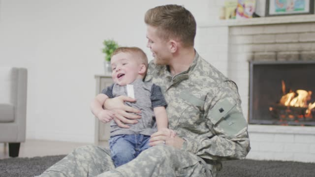 Soldier Father Playing With His Baby Boy A young adult father of caucasian descent is playing with his young. He has just returned from active duty and they are both smiling. military lifestyle stock videos & royalty-free footage