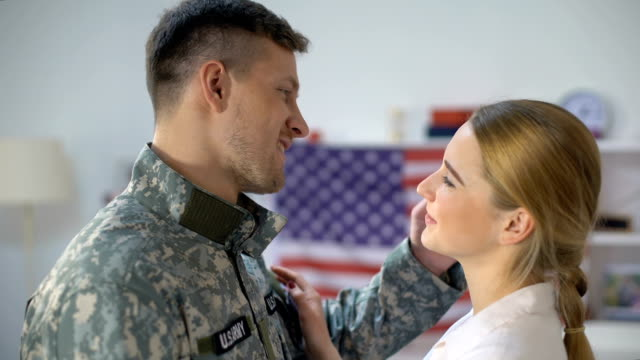 vídeos de stock e filmes b-roll de us soldier in uniform hugging girlfriend and smiling at cam homecoming after war - regresso ao lar