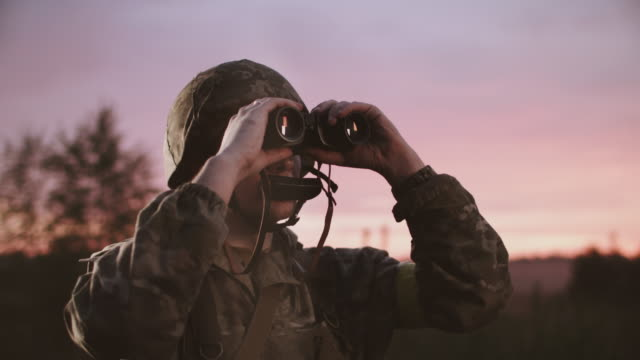 Soldier In Uniform Looks In Binoculars. Soldier In Uniform Looks In Binoculars. Twilight. Young Guy Takes Binoculars That Hangs From His Neck And Looks. camouflage clothing stock videos & royalty-free footage