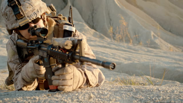 Soldier Lies Down on the Hill, Aims through the Assault Rifle Scope in Desert Environment. Slow Motion. video