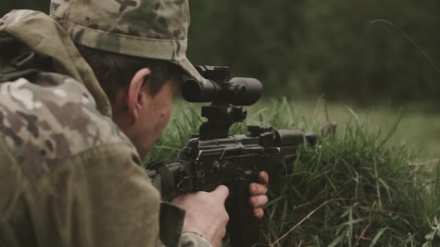 Soldier Looks At The Sight Of The Weapon. Man In Camouflage Clothing Lies In The Grass. Soldier Looks At The Sight Of The Weapon. Man In Camouflage Clothing Lies In The Grass. View From The Back. camouflage clothing stock videos & royalty-free footage