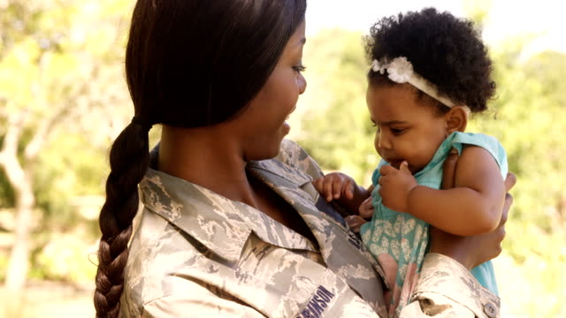 Soldier mother holding her daughter in a park Soldier mother holding her daughter in a park on a sunny day military uniform stock videos & royalty-free footage