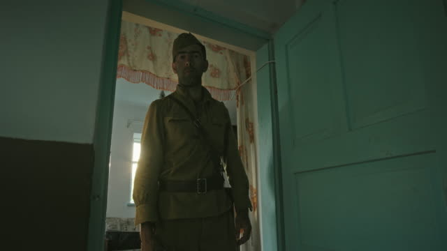 A soldier of the Red Army in World War II, in uniform, stands at the door of an old farmhouse and stares sadly at the camera. Bright sunlight shines through the window
