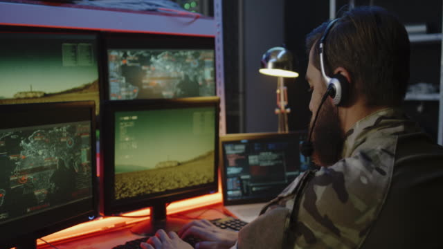 Soldier overseeing rocket launch on computer video