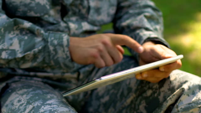 Soldier using tablet outdoors, online psychological support service for veterans Soldier using tablet outdoors, online psychological support service for veterans veteran stock videos & royalty-free footage