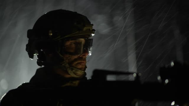 Soldier with Assault Rifle with Flashlight Between Trees.
