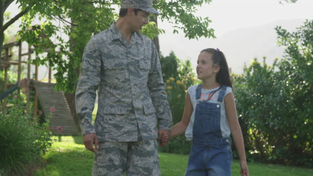 Soldier with his daughter Front view of a young adult mixed race male soldier in the garden outside his home, holding hands and walking and talking with his daughter, who is holding a US flag and looking up at him, slow motion military uniform stock videos & royalty-free footage