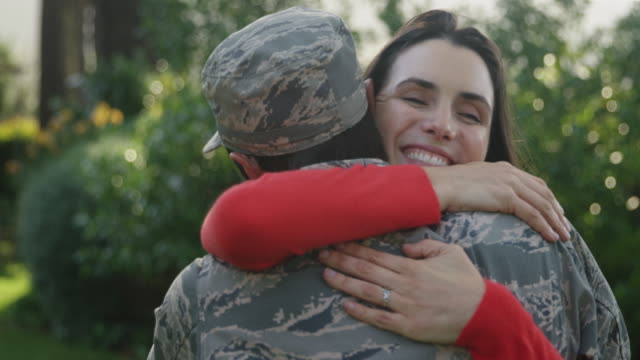 Soldier with his family Rear view of a young adult mixed race male soldier in the garden outside his home, embracing his young adult Caucasian female partner, who is smiling with eyes closed, slow motion military uniform stock videos & royalty-free footage