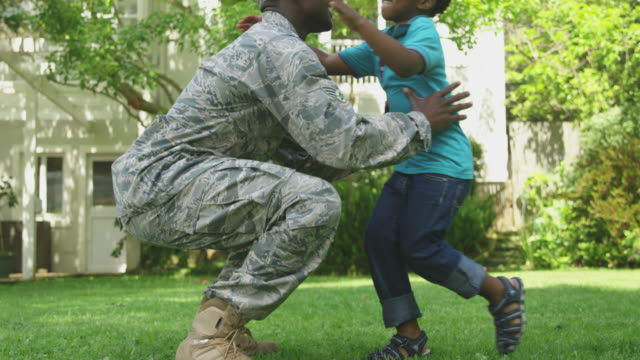 Soldier with his son Side view close up of a young adult African American male soldier kneeling in the garden outside his home, greeting his young son, picking him up, standing and embracing him, both smiling, their house in the background, slow motion military uniform stock videos & royalty-free footage