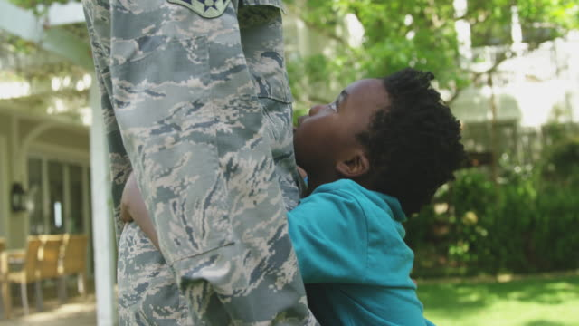 Soldier with his son SIde view mid section of a young adult African American male soldier in the garden outside his home, embracing his young son, who is looking up at him smiling and holding a US flag, thier house in the background, slow motion military uniform stock videos & royalty-free footage
