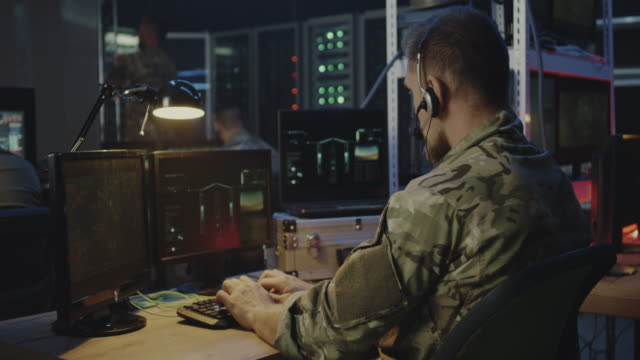 soldiers controlling rocket launch on computer - azionare video stock e b–roll
