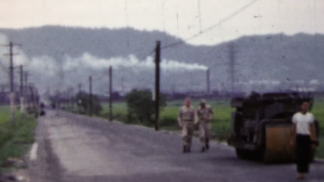 1951: Soldiers exploring Japanese countryside rice fields steamroller. video