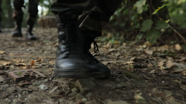 Soldiers in the woods Group of unrecognizable men in military uniform walking in the woods,low section,slow motion camouflage clothing stock videos & royalty-free footage