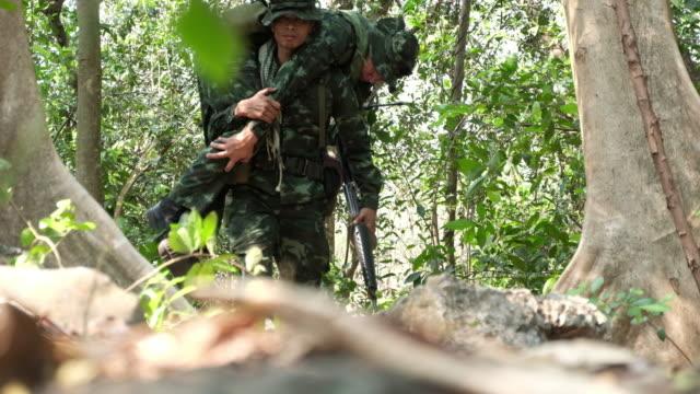kaydetme ve onların yaralı yoldaş yıkık bina taşıyan askerler - açık yara stok videoları ve detay görüntü çekimi