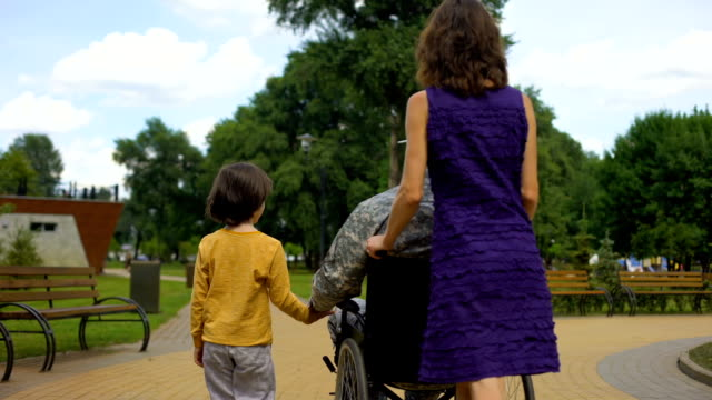 soldiers wife assisting disabled husband in wheelchair, family rest in park - military lifestyle stock videos & royalty-free footage