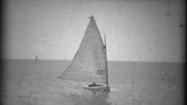 1934: Solo fancy sailboat coming into the pier for the day. video