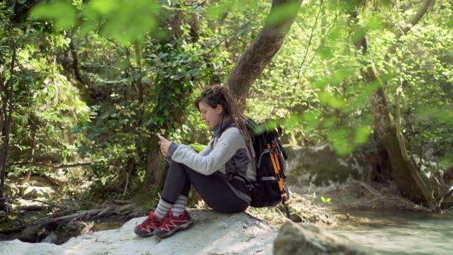 solo female hiker using smart phone - woman portrait forest video stock e b–roll
