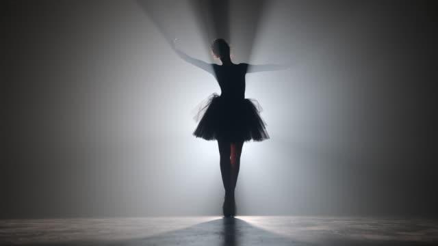 劇場で発光ネオンスポットライトを背景に、チュチュドレスのバレリーナによるソロパフォーマンス。古典的な動きを踊るポイントシューズの女性のシルエット。4k. - バレリーナ点の映像素材/bロール