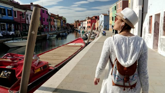 solo traveler, young woman tourist walking on burano island, venice, italy. city of romance with its typical venetian sights. - italian architecture stock videos & royalty-free footage