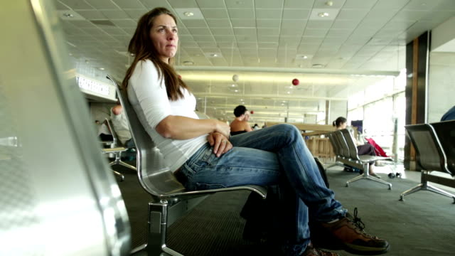 Solo Woman Traveler at Airport waiting to Board Plane video