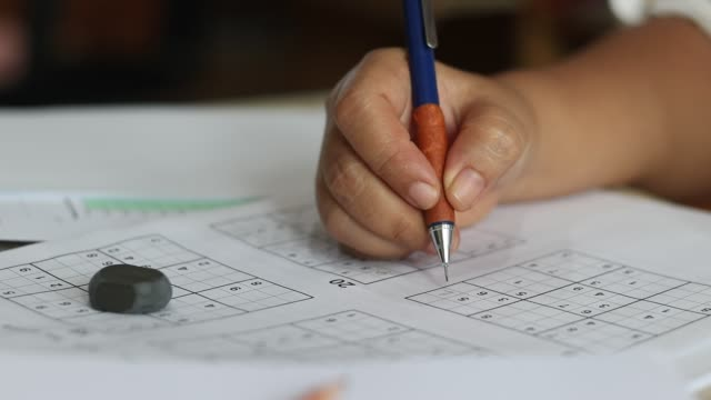 Solve sudoku puzzle with pencil as hobby by senior woman on wooden office desk. Player insert numbers into grid consisting of nine squares subdivided into further nine smaller squares.
