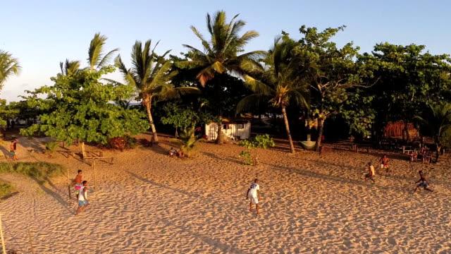 Alguns homens jogando futebol na praia - vídeo