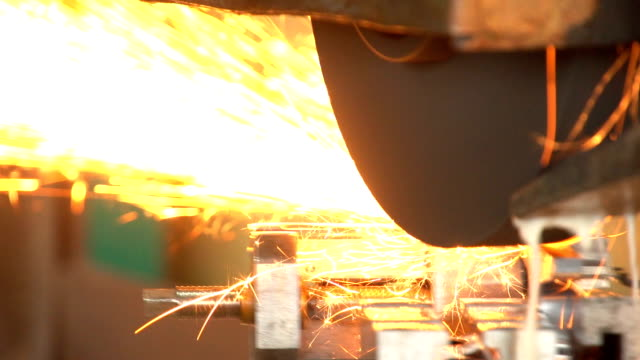 Some moving device grinds some metal surface with astream of sparkle at a plant video
