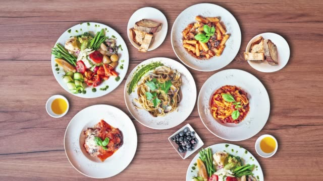Some Plates of Delicious italian food on Textured wooden background, top view Some Plates of Delicious italian food on Textured wooden background, top view table top view stock videos & royalty-free footage