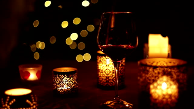 Somebody pours wine into a glass with candles around and a Christmas tree in the backdrop video