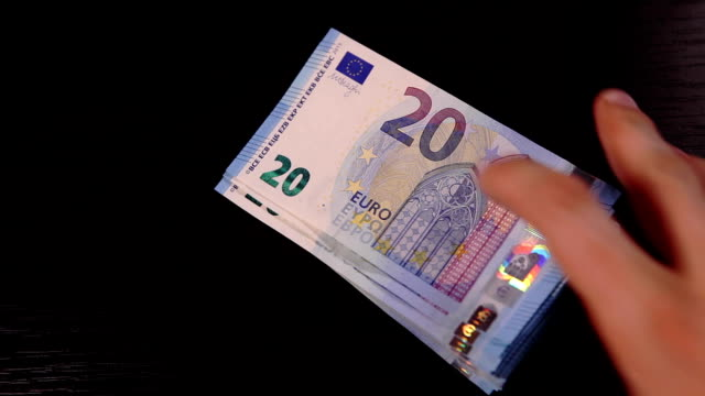 Somebody puts pack of 20-euros banknotes on the black table video