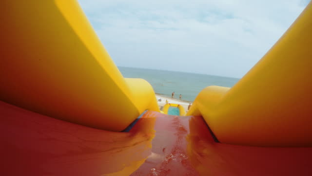 somebody slides fast by the inflatable slide into the water pool - scivolo video stock e b–roll