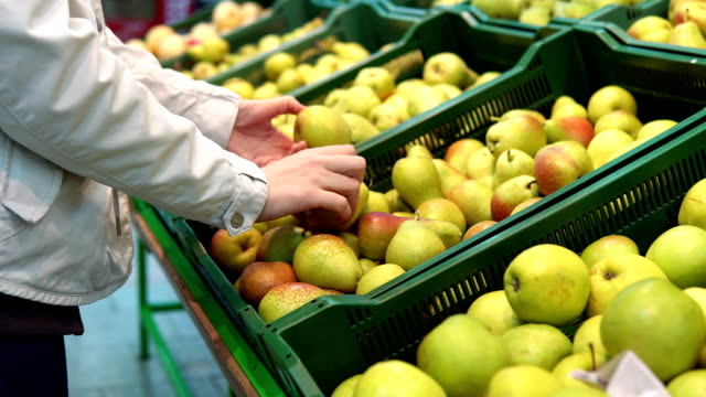 Someone chooses pears in the supermarket. Someone selects pears in the supermarket. Female hand chooses green fruits in the vegetable department at the grocery store. pear stock videos & royalty-free footage