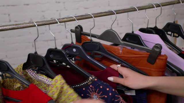 någon att välja kläder i en butik - köpnarkoman bildbanksvideor och videomaterial från bakom kulisserna