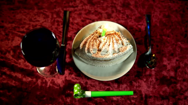 Someone extinguishes a burning candle in a festive cake, a holiday background. video