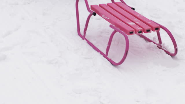 Someone is pulling an empty pink sled through the snow