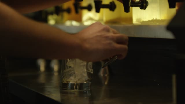 Someone Pours a Shot into a Glass A Caucasian hand pours clear alcohol from a glass drink dispenser into a metal shot glass and then pours that into a clear glass with ice in it, spilling some in the process. tonic water stock videos & royalty-free footage