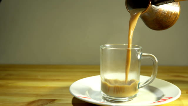 Someone pours hot coffee into a transparent cup video