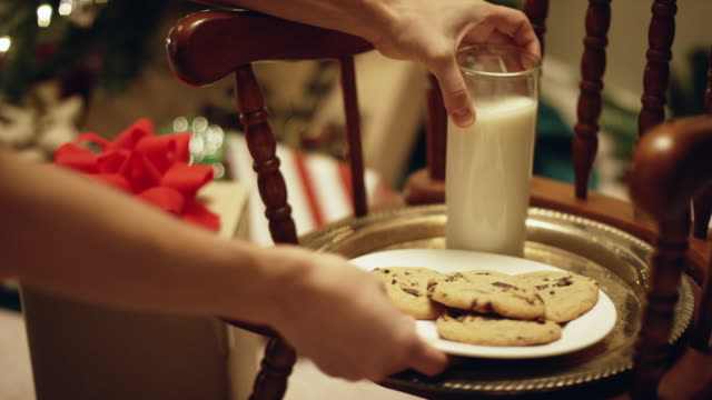 vídeos de stock e filmes b-roll de someone sets a plate of milk and cookies on a platter next to a christmas present on christmas eve - christmas cookies