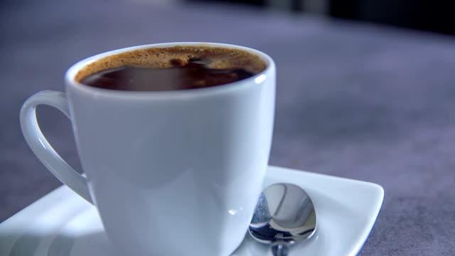 något faller i svart kaffe på ett bord - tefat bildbanksvideor och videomaterial från bakom kulisserna