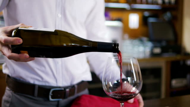 Sommelier filling glass with wine in restaurant, close up, slow motion video