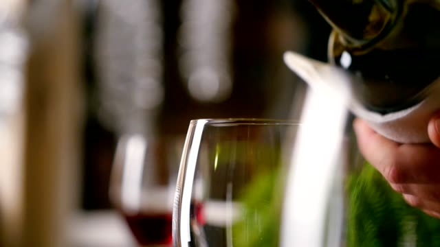 Sommelier filling glass with wine in restaurant video