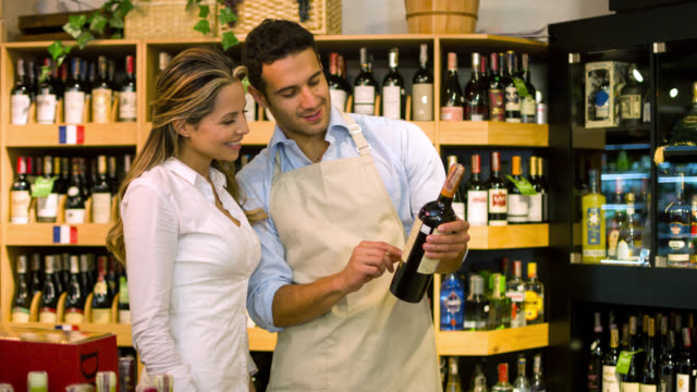 Sommelier helping woman at the supermarket buying wine video
