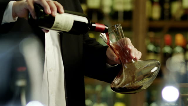 sommelier pouring red wine into decanter. - fine dining stock videos and b-roll footage
