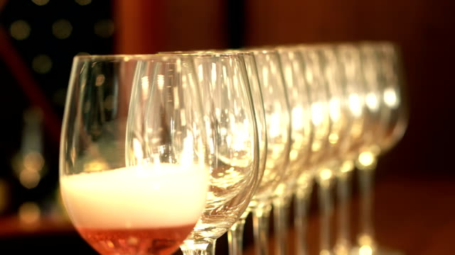 Sommelier pouring rose wine into a row of crystal glasses video