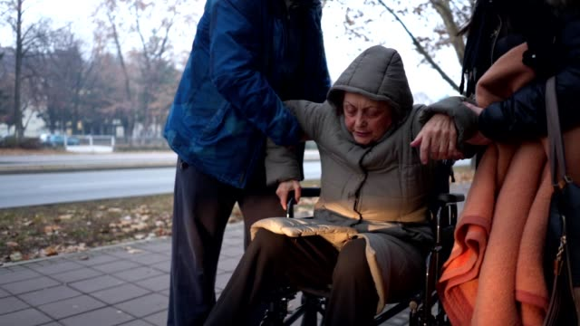 figlio e figlia che aiutano la madre anziana ad alzarsi dalla sedia a rotelle - fragilità video stock e b–roll