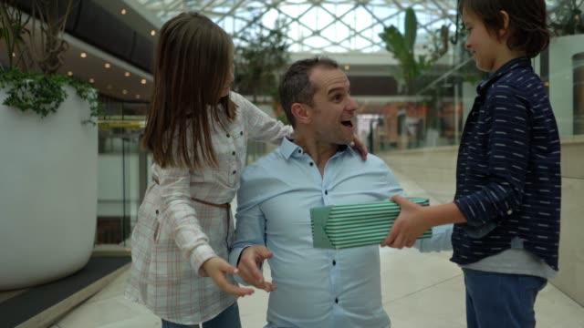 息子と娘は、彼がそれらを抱擁し、笑顔ながら、父の日のプレゼントとモールで彼らのお父さんを驚かせます - 父の日点の映像素材/bロール