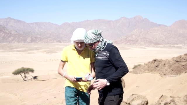 Sohn und Vater in der Wüste berühren Smartphone – Video