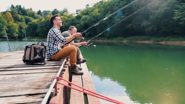 son and father sitting on jetty and fishing - campeggio video stock e b–roll