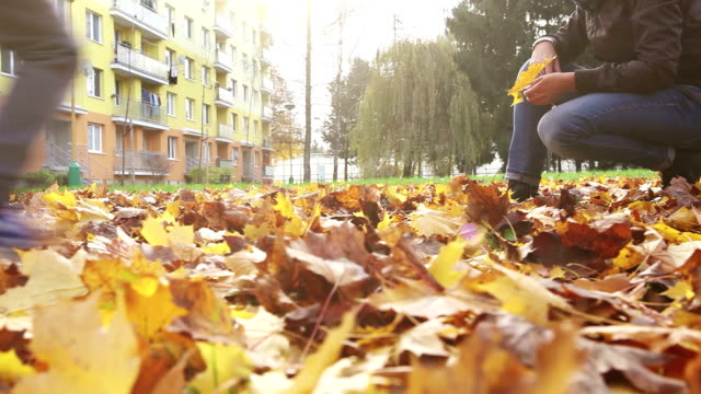 Son comes to his mum, hugs her and gives her a bundle of yellow autumn leaves video